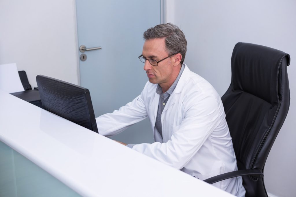 High angle view of dentist sitting by computer